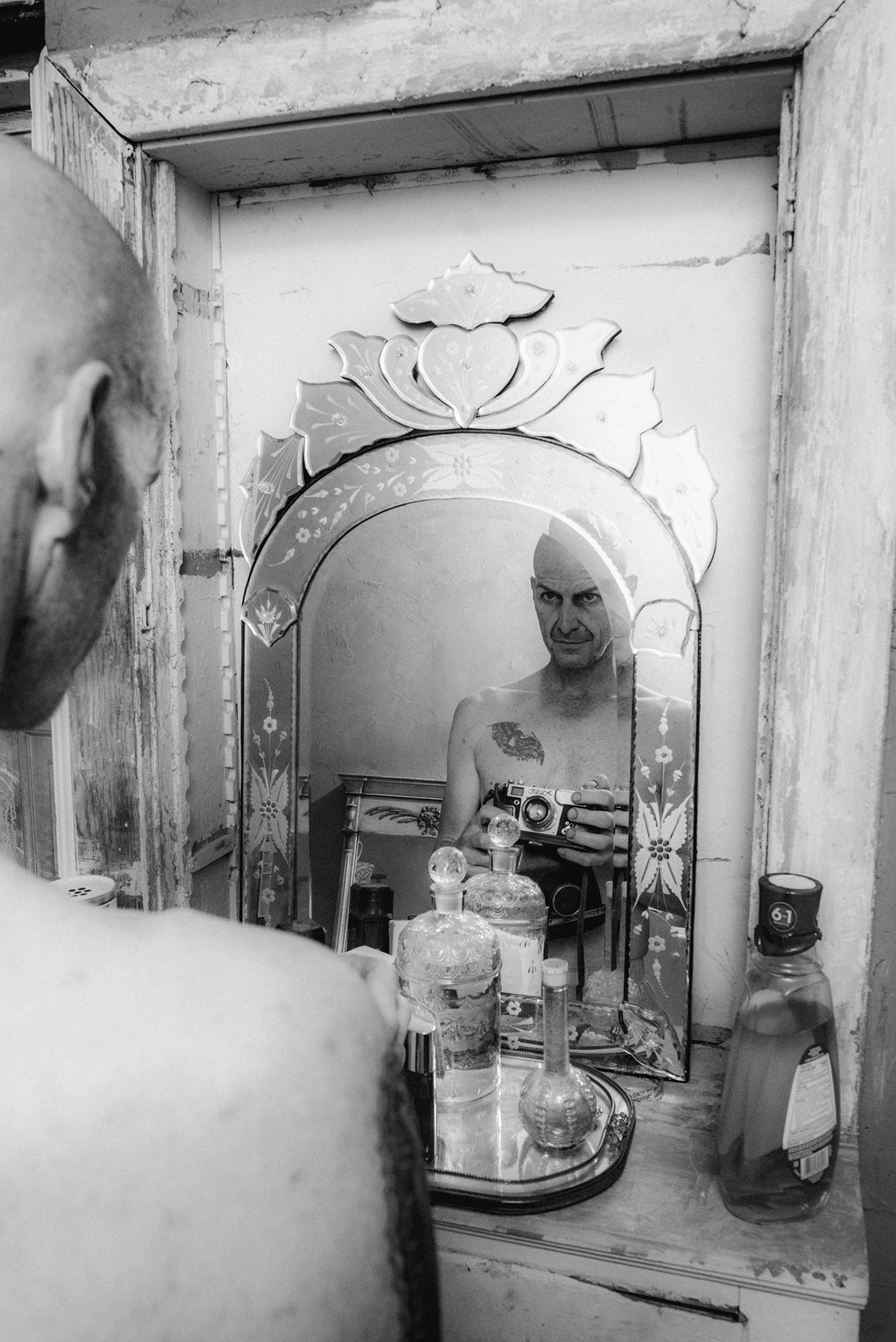 Denis Ohare looking into a mirror in lady gaga v magazine shoot by Chadwick Tyler american horror show