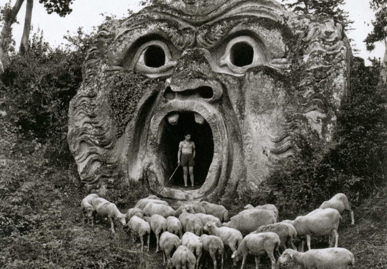 Black and white Mysterious photo of a shepherd with sheep in the mouth of a stone carved face