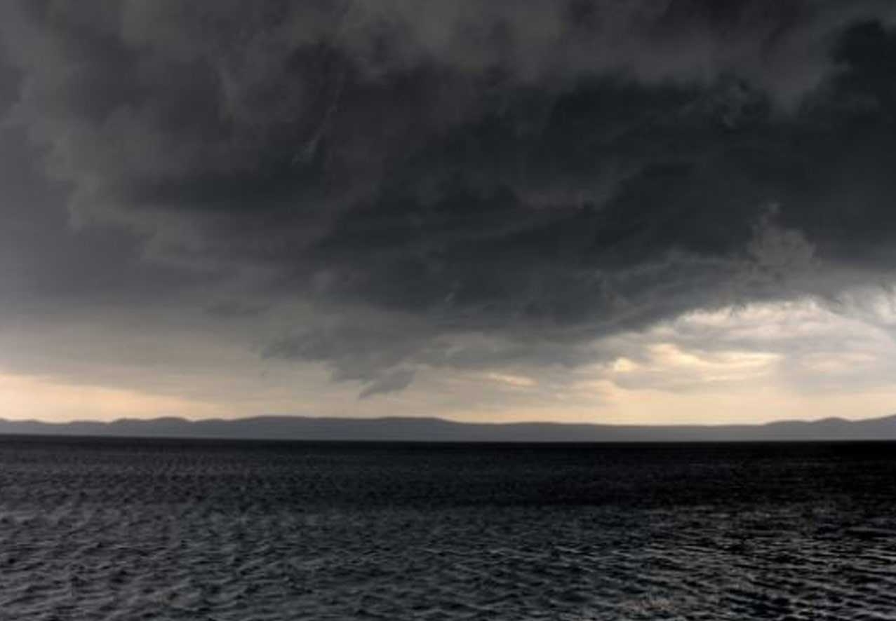A photo of a the sea, the sky, and clouds. the Sky pale orange but the clouds and ocean are dark black